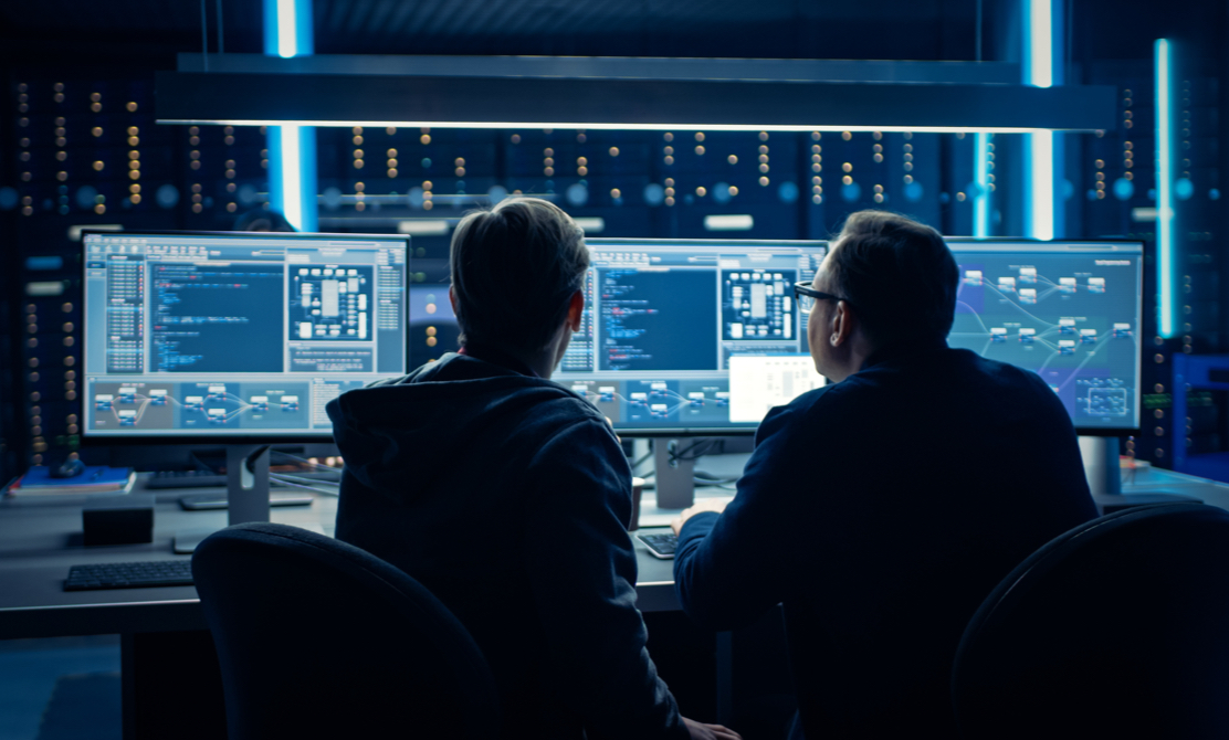 Two Professional IT Programers Discussing Blockchain Data Network Architecture Design and Development Shown on Desktop Computer Display